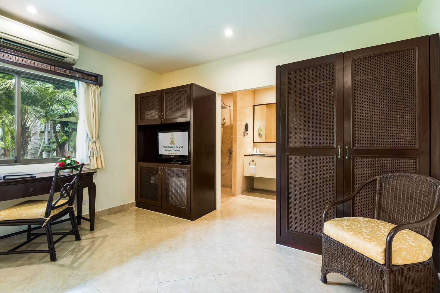 working desk and wardrobe of a superior hotel room with a garden view of the Thai Garden Resort in Pattaya, Thailand.