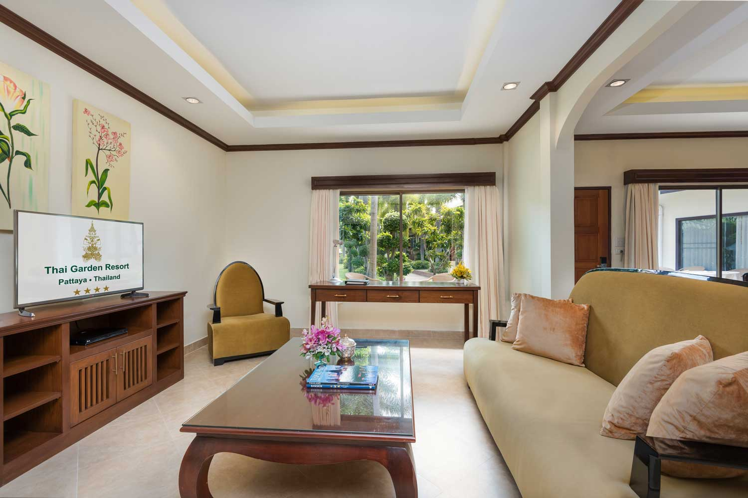 The living room of a two-Bedroom Apartment hotel room with a garden view of the Thai Garden Resort in Pattaya, Thailand