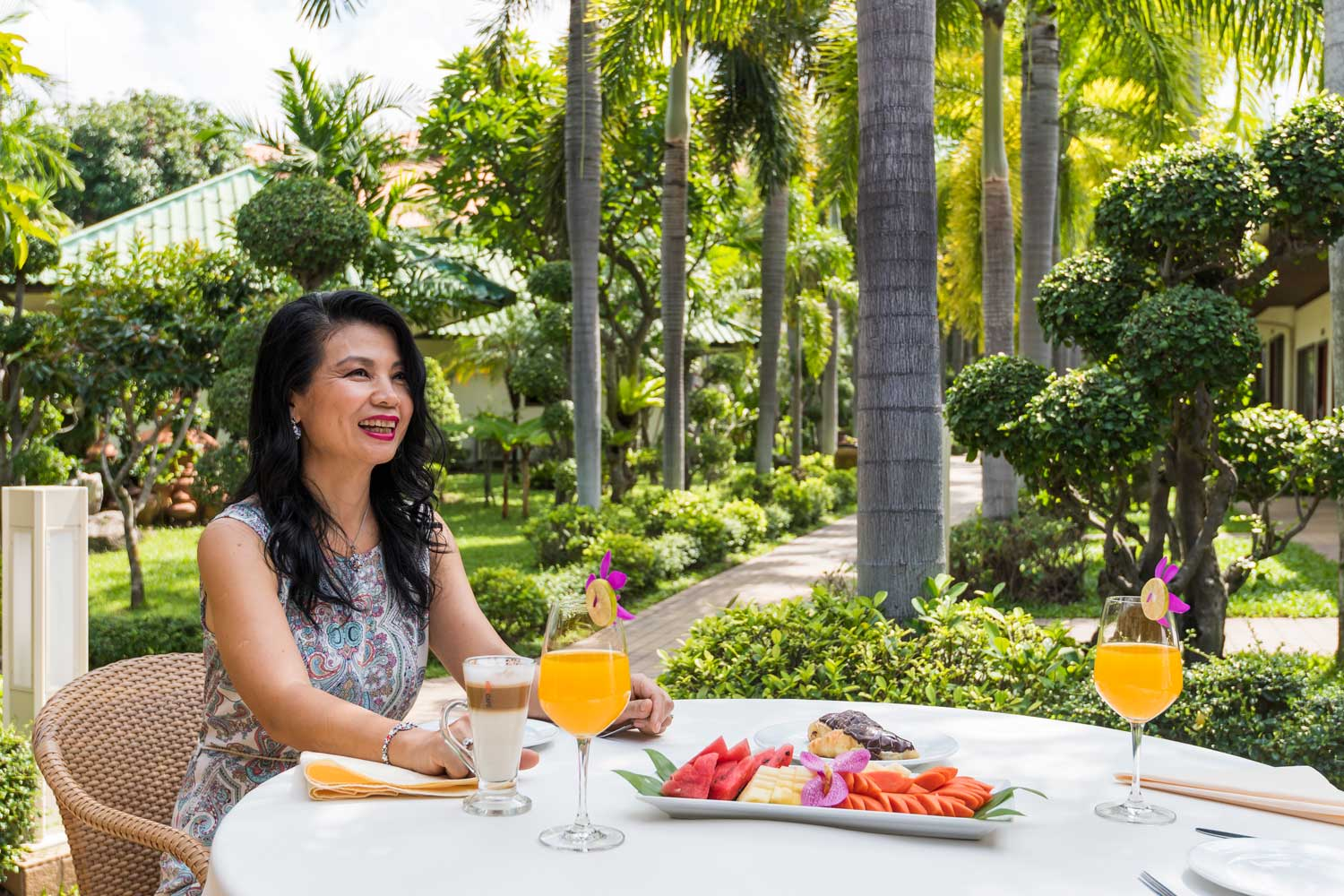 Woman enjoying breakfast on a table in the garden of the Thai Garden Resort in Pattaya, Thailand