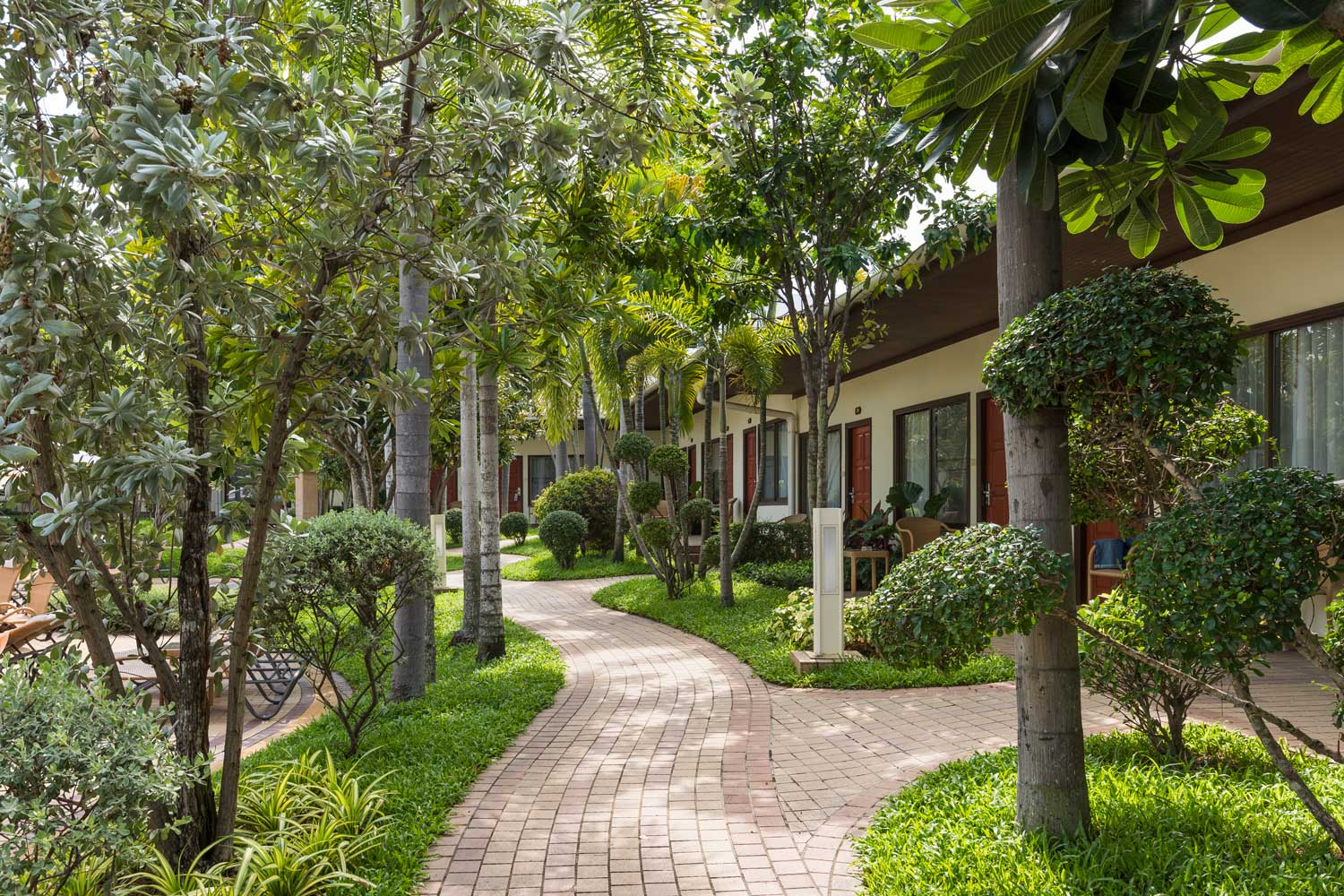 Walkway with trees in the garden of Thai Garden Resort in Pattaya, Thailand