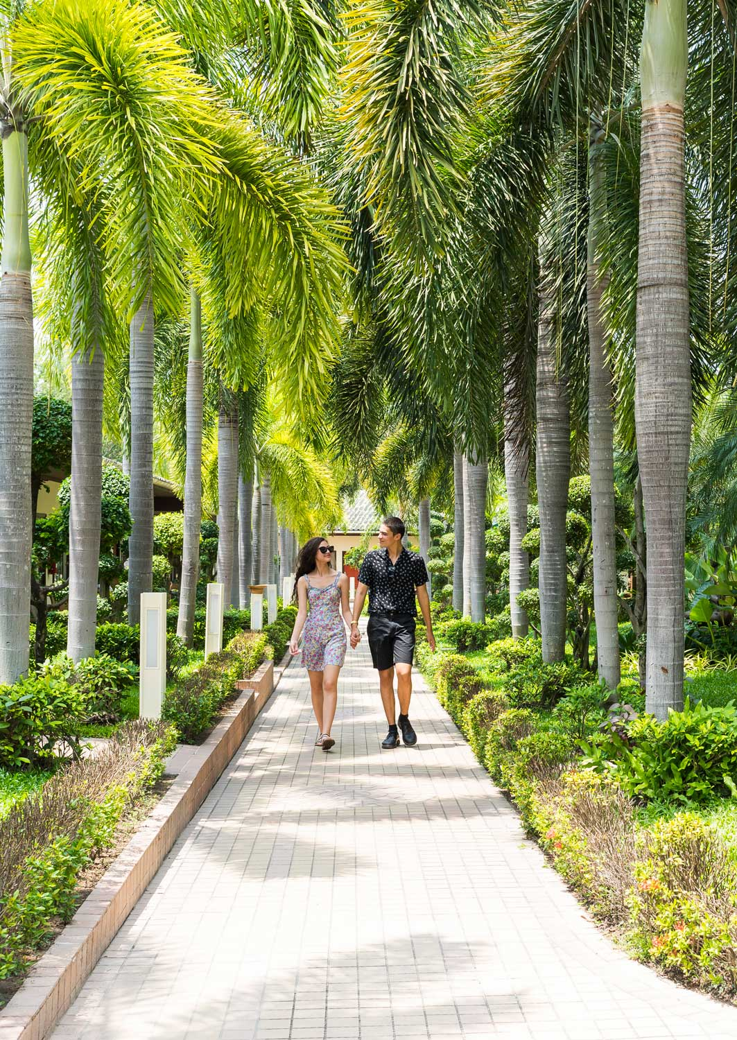 couple walking on a walkway under Palm trees in the tropical garden of the Thai Garden Resort in Pattaya, Thailand