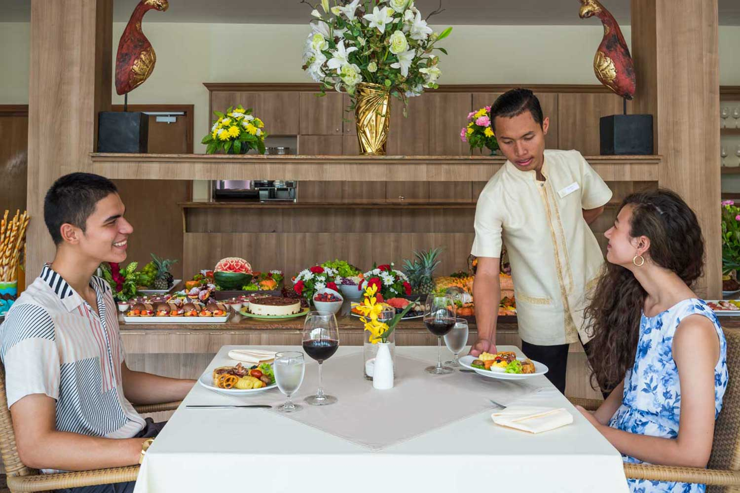 Couple getting served by a waiter in the Oasis restaurant of the Thai Garden Resort in Naklua in Pattaya, Thailand
