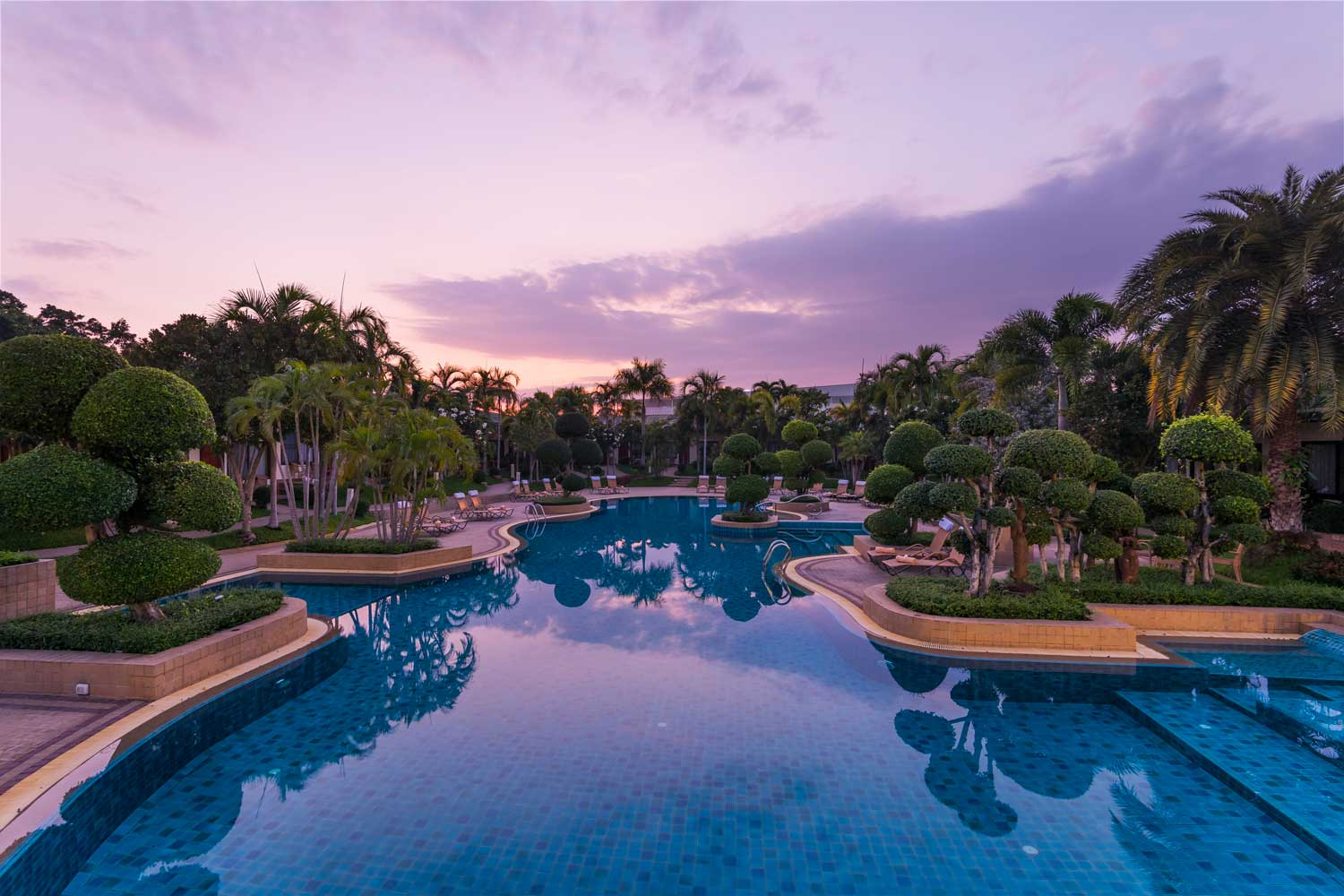 Sunrise over the tropical garden and the large swimming pool at Thai Garden Resort in Pattaya, Thailand