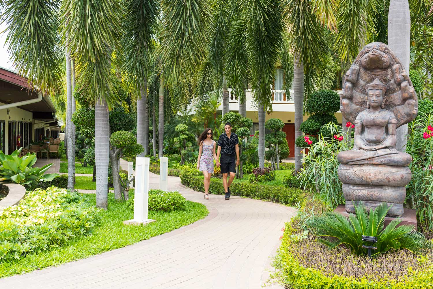 Couple walking in the under Palm Trees at Thai garden Resort in Pattaya Thailand